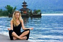 Menina que meditating no lago em Bali Imagem de Stock