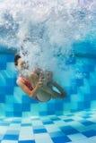 Menina que mergulha debaixo d'água na piscina Fotos de Stock