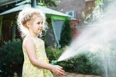 Menina que molha a grama no jardim Fotos de Stock Royalty Free