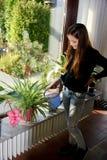 Menina que molha os houseplants fotografia de stock royalty free