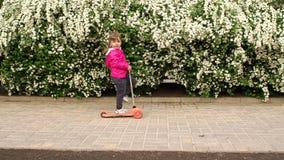 Menina que monta seu 'trotinette' no parque, mo lento vídeos de arquivo