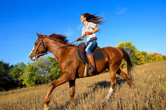 Menina que monta um cavalo