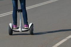 Menina que monta um giroscópio em uma estrada de passeio Fotografia de Stock Royalty Free