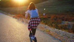 Menina que monta um 'trotinette' bonde na maneira ao por do sol, opinião lenta da parte traseira do mo vídeos de arquivo