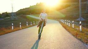 Menina que monta um 'trotinette' bonde no por do sol atrás vídeos de arquivo