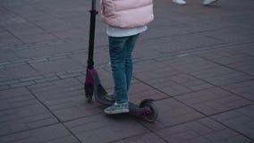 Menina que monta um 'trotinette' na rua Close-up dos pés do 'trotinette' vídeos de arquivo