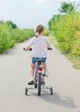 Menina que monta uma bicicleta Fotografia de Stock
