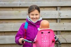 Menina que monta uma bicicleta com uma boneca A criança está montando uma bicicleta imagem de stock