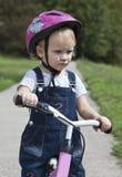 Menina que monta uma bicicleta em um parque Fotografia de Stock