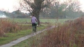 Menina que monta uma bicicleta na fuga video estoque