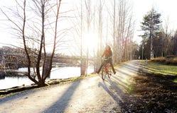 Menina que monta uma bicicleta no parque Foto de Stock