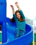 Menina que monta uma corrediça. Imagem de Stock