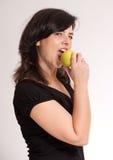 Menina que morde uma maçã Foto de Stock