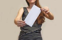 Menina que mostra aslant a brochura branca vazia do folheto do inseto leaflet foto de stock