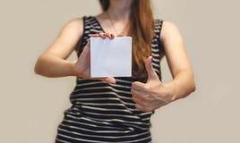 Menina que mostra a brochura vazia do folheto do inseto do quadrado branco leaflet fotografia de stock