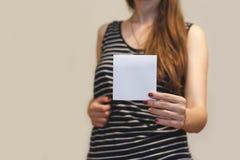 Menina que mostra a brochura vazia do folheto do inseto do quadrado branco leaflet imagem de stock royalty free