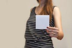 Menina que mostra a brochura vazia do folheto do inseto do quadrado branco leaflet fotos de stock