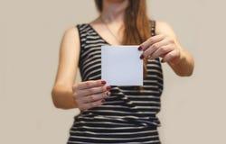 Menina que mostra a brochura vazia do folheto do inseto do quadrado branco leaflet foto de stock