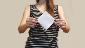 Menina que mostra a brochura vazia do folheto do inseto do quadrado branco leaflet fotos de stock royalty free