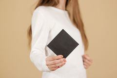 Menina que mostra a brochura vazia do folheto do inseto do quadrado preto leaflet fotografia de stock