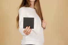 Menina que mostra a brochura vazia do folheto do inseto do quadrado preto leaflet imagem de stock