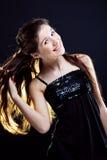 Menina que mostra o cabelo bonito no preto Fotografia de Stock