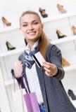 Menina que mostra o cartão de crédito na loja dos calçados Foto de Stock