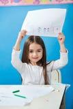 Menina que mostra o papel de desenho no pré-escolar Imagens de Stock Royalty Free