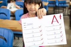 Menina que mostra o papel do exame Fotografia de Stock Royalty Free