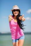 Menina que mostra os polegares acima na praia Foto de Stock Royalty Free