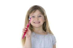Menina que mostra sua escova de dentes Foto de Stock