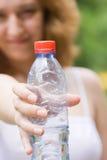 Menina que mostra um frasco da água imagens de stock royalty free