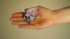 Menina que mostra uma caixa de presente em sua mão, em um fundo claro, fim acima, movimento lento video estoque