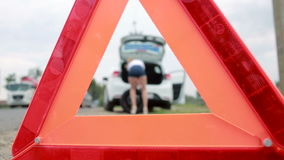 Menina que muda um pneu puncionado no carro reparo dos carros na estrada acidente filme
