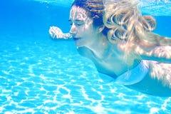 Menina que nada o retrato subaquático Fundo da água azul do verão do mar com dia ensolarado das bolhas Fotos de Stock