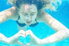 Menina que nada o retrato subaquático Símbolo do sinal do amor Fundo da água azul do verão do mar com bolhas Fotografia de Stock Royalty Free