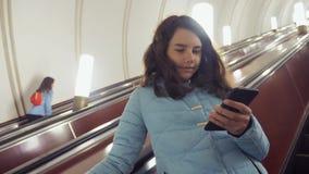 A menina que o adolescente no metro subterrâneo monta em uma escada rolante, estilo de vida guarda o smartphone filha moreno da m video estoque