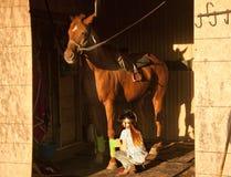 A menina que obtém seu cavalo selado e apronta-se para montar Imagens de Stock