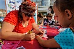 Menina que obtém a tatuagem do brilho Tyumen Rússia Foto de Stock