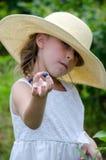 Menina que oferece um mirtilo Imagem de Stock