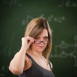 Menina que olha acima de seus vidros de leitura Fotografia de Stock Royalty Free
