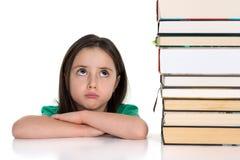 Menina que olha acima na pilha dos livros Imagens de Stock Royalty Free