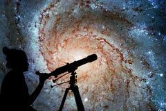 Menina que olha as estrelas com telescópio Galáxia do girândola Foto de Stock