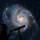 Menina que olha as estrelas com telescópio Galáxia do girândola Foto de Stock Royalty Free