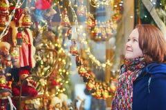 Menina que olha as loja-janelas decoradas para o Natal Fotografia de Stock Royalty Free