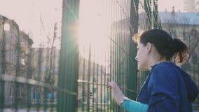 Menina que olha atrás de uma cerca, 4k video estoque