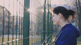 Menina que olha atrás de uma cerca, 4k vídeos de arquivo