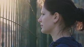 Menina que olha atrás de uma cerca, movimento lento, 120fps video estoque