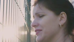 Menina que olha atrás de uma cerca, movimento lento, 120fps vídeos de arquivo