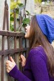 Menina que olha através da cerca Fotografia de Stock Royalty Free